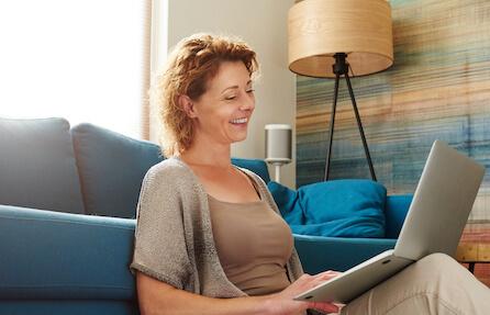 Na obrázku sedí u počítače veselá žena na online terapii